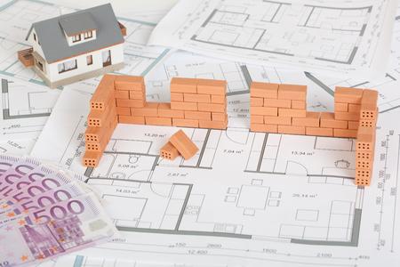Modelwoningbouw met baksteen op blauwdruk en vijfhonderd euro biljet Stockfoto