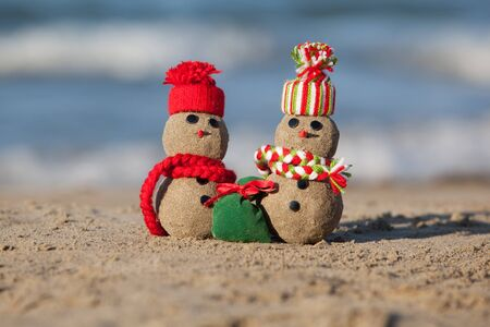 Two small sandy snowmen at tropical beach. Holiday concept - New Year's and Christmas Cards