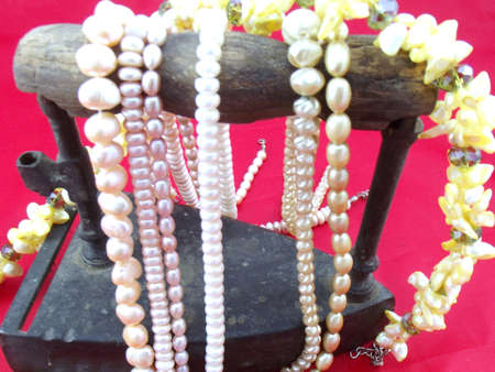 finesse: necklaces of pearls on red background