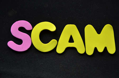 scamming: word scam on a black Stock Photo