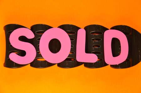 adjudicate: word sold on a orange Stock Photo