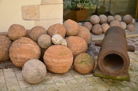 stone cannonballs and an iron cannon photo