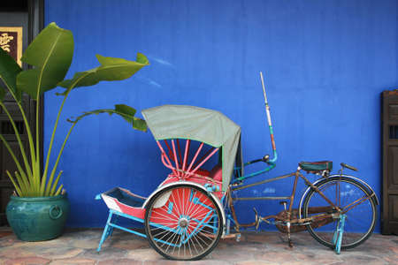 rickshaw: Traditional trishaw kept in Cheong Fatt Tze Mansion, aka the Blue Mansion in Penang, Malaysia. Stock Photo
