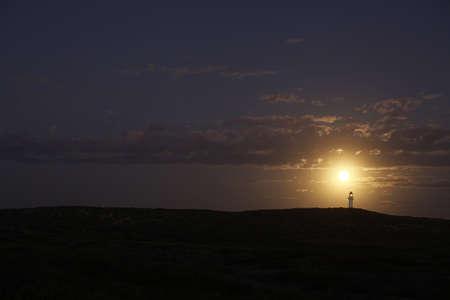 Full moon against lighthouse, Point Quobba, Western Australia. photo