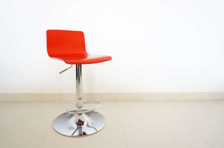 red chair: Red bar stool on white background on the tiled floor.  Stock Photo