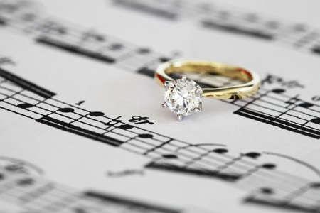 Ideal cut solitaire diamond on yellow gold onto music score.  Stock Photo