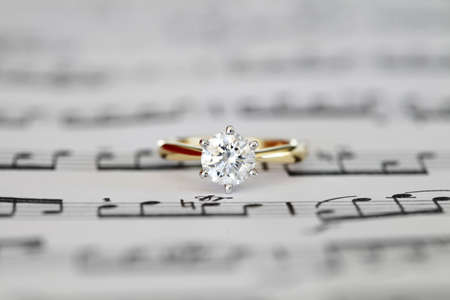 Ideal cut solitaire diamond on yellow gold ring onto music score. Top view.