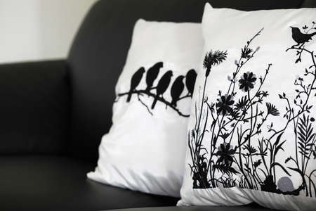 Black and white collection of pillow cases on black leather couch. Generic designs so no release needed.