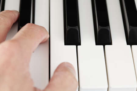 Playin the piano with fingers pressing on notes Stock Photo
