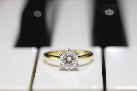 A big solitaire ideal cut diamond ring with piano key background. Stock Photo