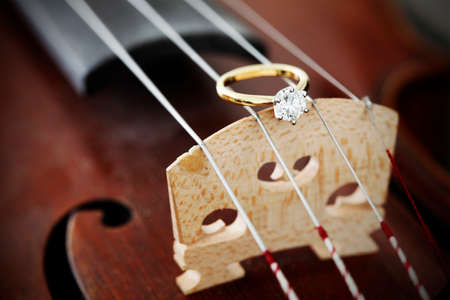 A big solitaire diamond ring on an antique violin.