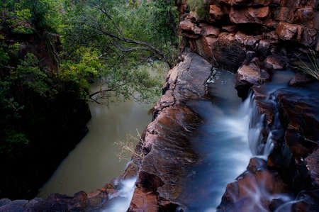 gorge: A waterfall flows into the depth in the majestic gorges of East Kimberley, Western Australia.