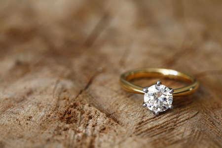 ソリティア婚約ダイヤモンド リングは、木製の有機背景を獲得しました。 写真素材