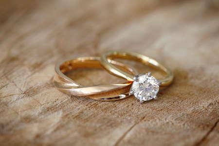 anillo de boda: Anillo solitario de diamante de compromiso con la alianza de boda en el fondo de madera orgánica. Foto de archivo