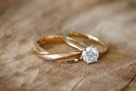 Solitaire engagement diamond ring with wedding band on wooden organic background.