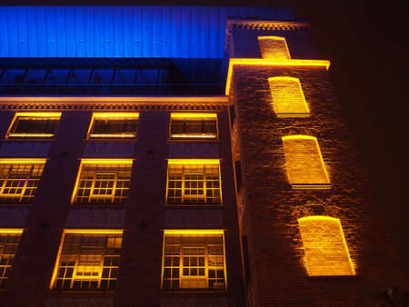 Beautiful building illuminated in yellow, red and blue Stock Photo