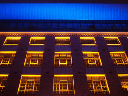 Beautiful brick building illuminated in yellow, red and blue Stock Photo