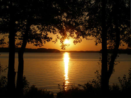 View of the lake and the setting sun on the forest line Stock Photo