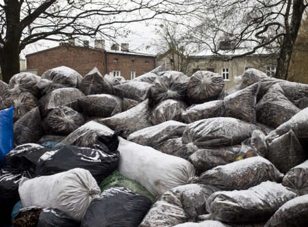 waste recovery: Bags of leaves and rubbish lying high up in front of the house Stock Photo