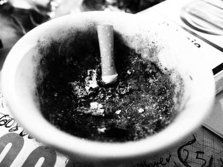 quenched: Cigarette in the ashtray next to a pack of cigarettes on a notebook Stock Photo
