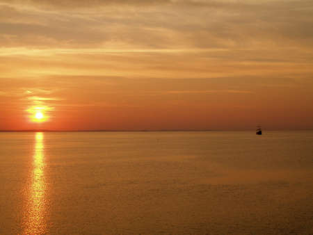 Red sunset over the Baltic Sea and flowing Columbus