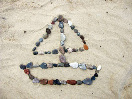 Sailboat made ​​of stones on the sand of a beach photo