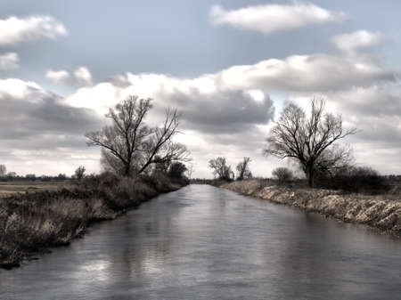 Lovely view of the river, trees, forest and fields on the background of clouds and sky Stock Photo
