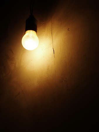 Dusty Incandescent light bulb on a dark wall background  photo