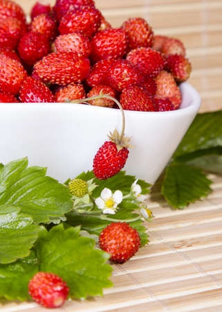 Wild strawberries in a small bowl, surrounded by leaves on the wooden pad photo