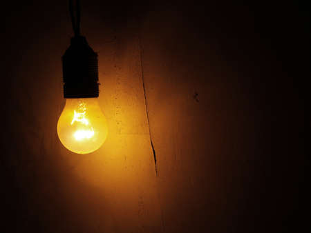 electric light: Dusty Incandescent light bulb on a dark wall background