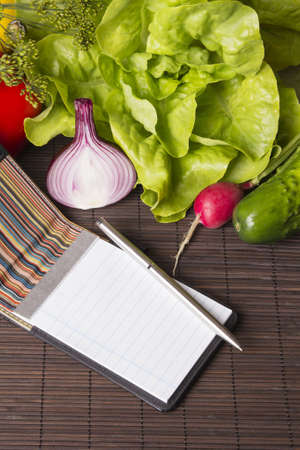 vegetables, notebook and pen on wood photo