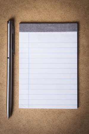 notebook and pen on a brown background photo