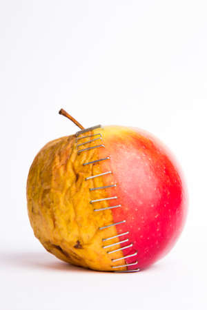 stapled apple halves, young and old, metaphor plastic surgery Stock Photo