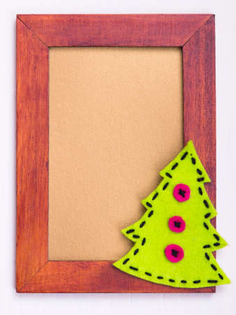 Christmas background, brown frame with a felt Christmas tree Stock Photo
