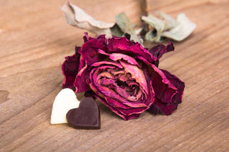 the dried rose and chocolate hearts on a wooden table photo
