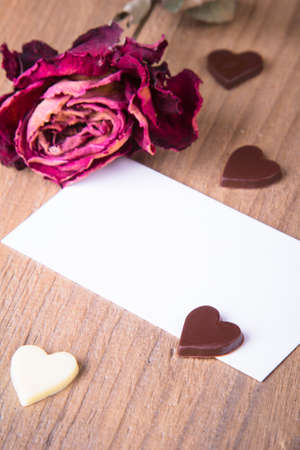 the dried rose, blank business card and chocolate hearts photo