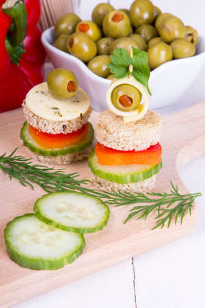 finger foods  bread, peppers, cucumber, cheese and olives photo