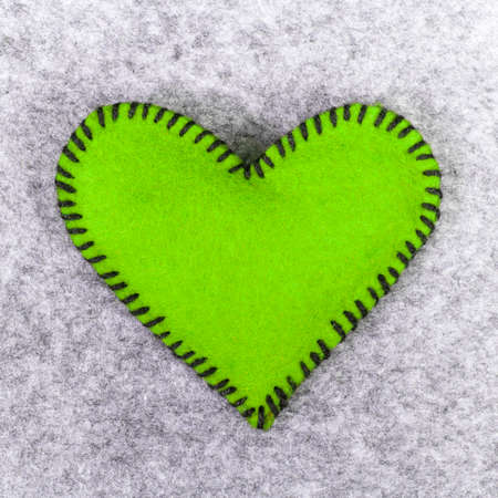 green felt heart on a gray background photo