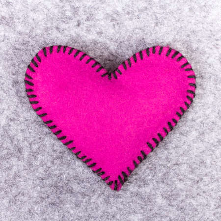 pink felt heart on a gray background photo