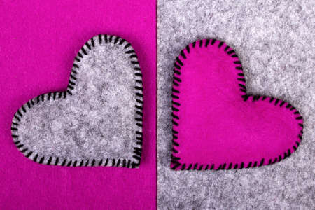 fitting in: two hearts  pink and gray on two different backgrounds, as a symbol of fitting in a relationship - valentine concept