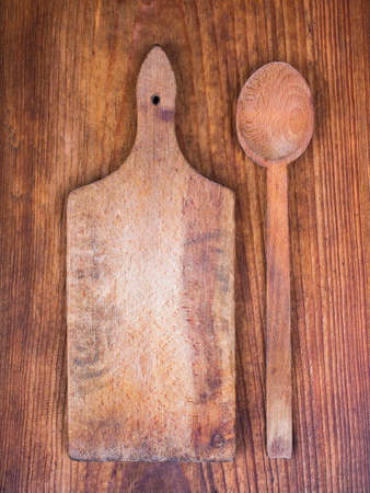 trencher: wooden cutting board and spoon on a wooden background