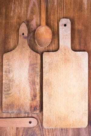 trencher: two wooden cutting boards and spoon on a wooden background