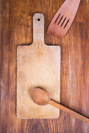 cutting board, spoon and spatula, wooden background photo