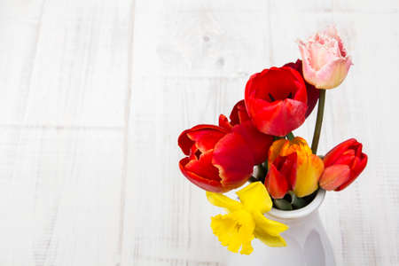 bouquet of tulips in a vase on a white wooden background photo