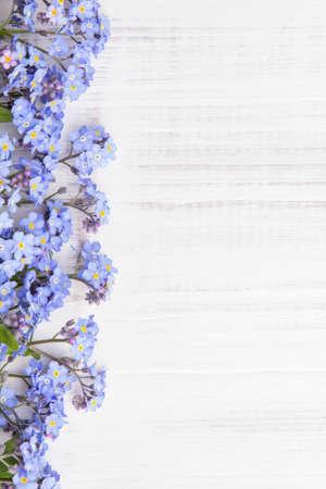 blauwe bloemen frame op witte houten achtergrond Stockfoto