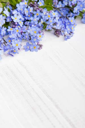 flores de cumplea�os: flores azules marco en el fondo de madera blanca