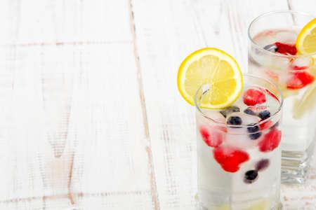 agua potable: agua mineral con fruta congelada en los cubos de hielo Foto de archivo