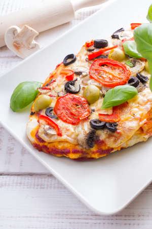 pizza with tomatoes, mushrooms, olives and peppers served on a plate on a wooden table Stock Photo