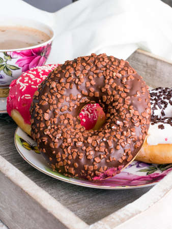donuts and cup of coffee on wood background