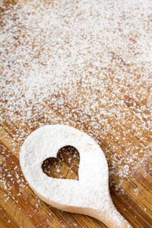 Heart hole spoon on the wooden pastry board - baking background Standard-Bild